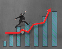 Businessman running and jumping on growth red arrow with chart Royalty Free Stock Photography