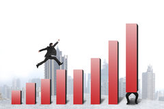 Businessman running, jumping on red bar chart another hold one Stock Photo