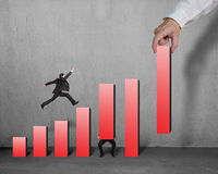Businessman running and jumping on red bar chart Royalty Free Stock Photography