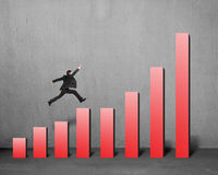 Businessman running and jumping on red bar chart Stock Photography