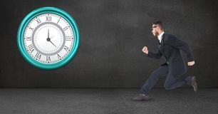 Businessman running late clock mounted on wall Stock Photos