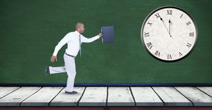 Businessman running late with clock mounted on wall Stock Photos