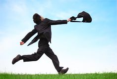 Businessman running on meadow with bag Stock Photo
