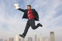 Businessman Running In Midair. Full length of mixed race businessman running in midair with newspaper Royalty Free Stock Images