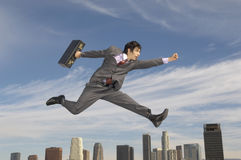 Businessman Running Midair Above City. Side view of a young businessman running with briefcase in midair above city stock images