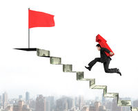 Businessman running on money stairs with arrow for top flag Royalty Free Stock Photos
