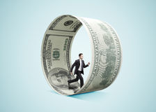 Businessman running in money wheel Royalty Free Stock Photography