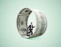Businessman running in money wheel Stock Image