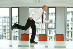 Businessman running on the office table Stock Image