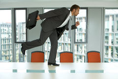 Businessman running on the office table Stock Photos