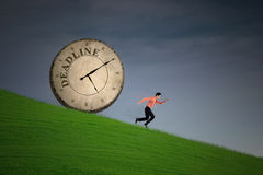 Businessman running out of deadline. Businessman is running with a clock chasing behind him on green field Stock Photo
