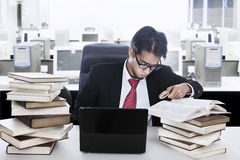 Businessman running out of time. Businessman holding a clock surrounded with books and laptop in his office Stock Photography