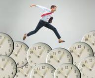 Businessman running over alarm clock. royalty free stock photo