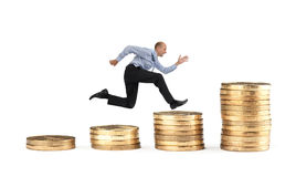Businessman running over coin stack Stock Photography