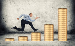 Businessman running over coin stack Stock Images