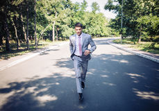 Businessman running in park Stock Photography