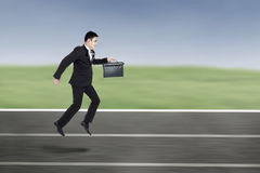 Businessman Running On A Racing Track Royalty Free Stock Image