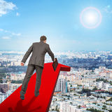 Businessman running on red arrow above city. Businessman on red arrow above city, rear view Stock Photos