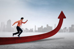 Businessman running on red arrow Royalty Free Stock Photos