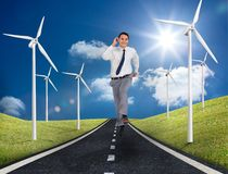 Businessman running on a road next to windmills Stock Images