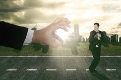 Businessman running scare being chased by a big hand Stock Photography