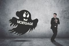 Businessman chased by a mortgage ghost. Businessman running scare being chased by a mortgage ghost while carrying a briefcase stock images
