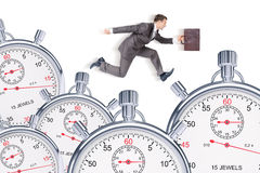 Businessman running with set of timers Stock Photo