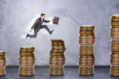 Businessman running on stack of coins Royalty Free Stock Photos
