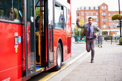 Businessman Running To Catch Bus Stop. Raising His Arm Royalty Free Stock Photo