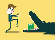 Businessman running to money in crocodile's mouth. Business and finance risk. Royalty Free Stock Images
