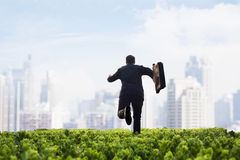Businessman running towards the city with a briefcase in a green field with plants Stock Image