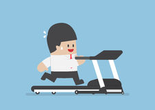 Businessman running on treadmill Stock Image