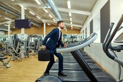 A businessman is running on a treadmill in the gym Stock Images