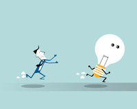 Businessman running  and trying to catch a big light bulb Royalty Free Stock Photo