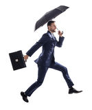 Businessman running with umbrella and briefcase. royalty free stock photography