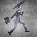 Businessman running with umbrella and briefcase. royalty free stock photo