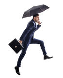Businessman running with umbrella and briefcase. royalty free stock images