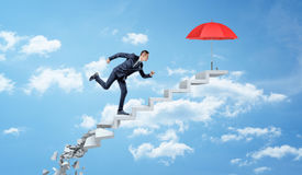 A businessman running up on crumbling concrete steps through the clouds to reach a red umbrella. Business protection. Hostile market environment. Survival Royalty Free Stock Photos