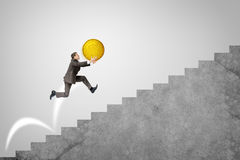 Businessman running up stairs holding big coin Royalty Free Stock Images