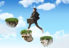 Businessman running up steps of floating rock platforms in sky. Digital composite of Businessman running up steps of floating rock platforms in sky Stock Image