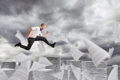 Businessman runs away from the worksheets and bureaucracy. Businessman jumps over columns of paper sheets royalty free stock photography