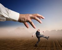 Businessman runs from a big arm. Businessman runs in a desert from a big arm Royalty Free Stock Image