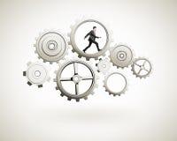 Businessman runs in gears Stock Image