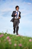 Businessman runs on grass Stock Images