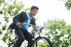 Businessman in a rush. Image of an active modern businessman riding a bicycle viewed below Stock Image