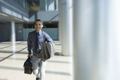 Businessman rushing through office lobby Royalty Free Stock Photography