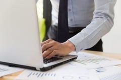 Businessman& x27; s entrega a análise de cartas e de gráficos e a datilografia em m foto de stock