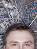 Businessman's face lying down on computer cables looking up, half Royalty Free Stock Images