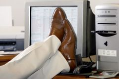 Businessman's Feet Propped Up On The Desk. An office worker puts his feet up on his desk in business success or in ignoring work to be done (focus point on the royalty free stock image