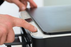 Businessman's finger pressing button of photocopy machine Royalty Free Stock Photography